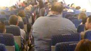 Photo: How Fat is Too Fat to Fly? This Man Hardly Looks Comfortable on the Airplane and Surly Isnt Seated Safely