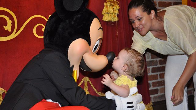 PHOTO: 18-month-old Ellie gives her new friend Mickey a kiss in Disneys Magic Kingdom, while Mom beams.