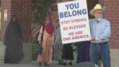 Justin Normand stood outside a mosque with a sign that read, You belong.