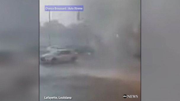Surveillance video outside a car repair shop in Lafayette, Louisiana shows a small twister touching down and flipping a parked car.