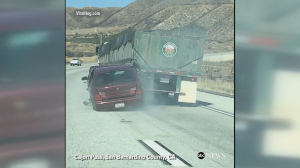 Dramatic video shows tractor-trailer dragging car 4 miles down California's Cajon Pass after the sedan became wedged under the truck.