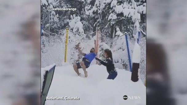 Colorado residents make the most of a massive snowfall in May by jumping on a snow-covered trampoline and having a snowball fight.