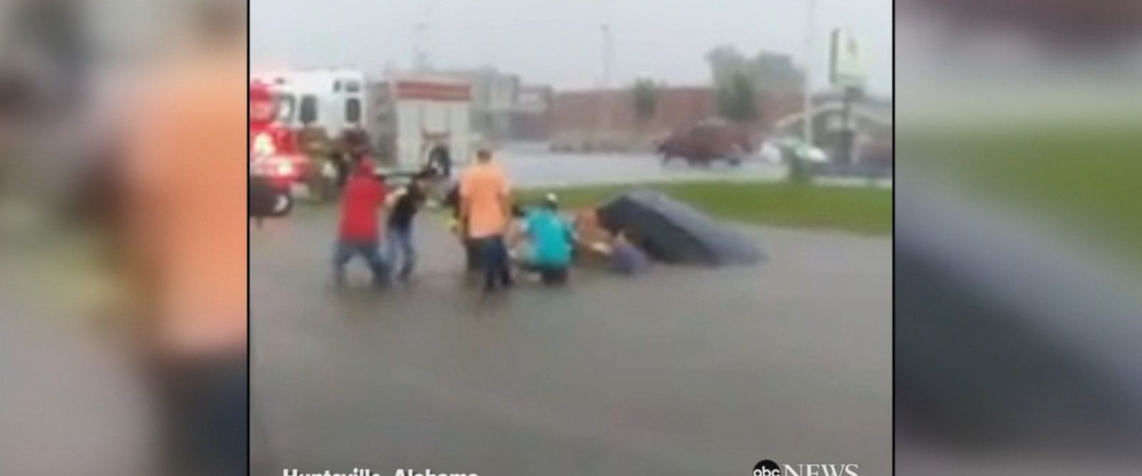 Good Samaritans work to free a driver stuck in her car after a flash flood swept her car into a ditch and was filling up with water.
