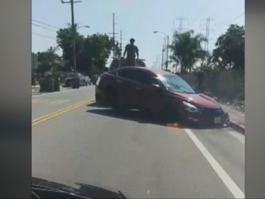WATCH:  Man stands on truck as car gets towed