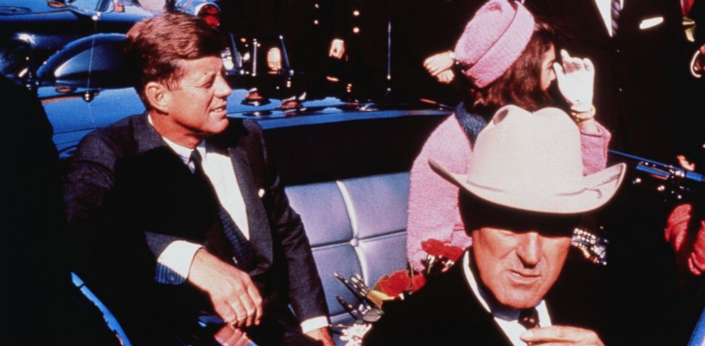 PHOTO: Texas Governor John Connally adjusts his tie (foreground) as President .John Kennedy and wife Jackie, in a pink outfit, settled in rear seats, prepared for motorcade into city from airport, Nov. 22 1963.