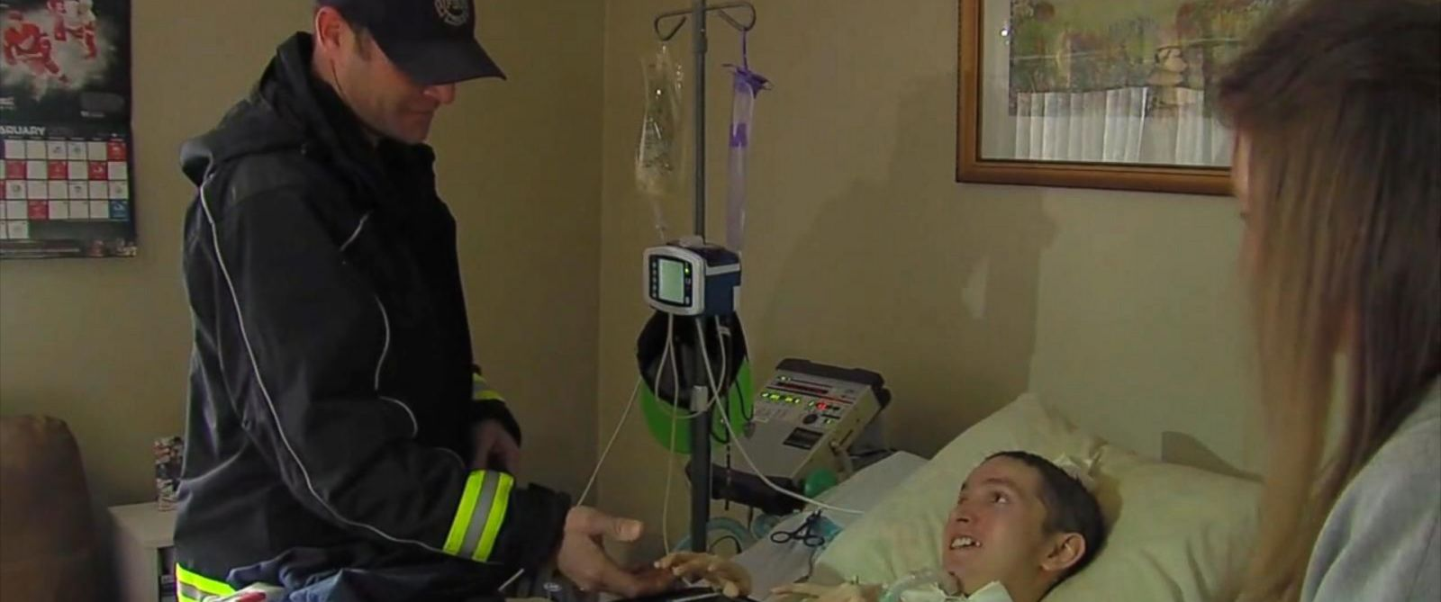 PHOTO: Firefighter Ryan McCuen, left, visiting with Troy Stone. McCuen paid the families electric bill when he responded to a call at their home and realized that Troys ventilator was not working because the power had been turned off.