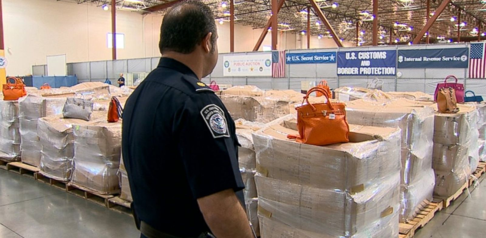 PHOTO: An officer looks at a shipment of seized counterfeit Hermes bags