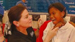 PHOTO: Tani Austin of the Starkey Hearing Foundation helps fit a hearing aid for a girl in Cambodia.