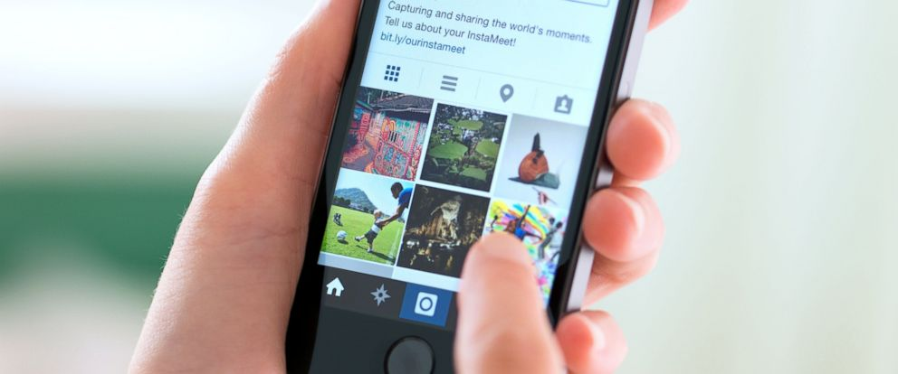 A woman is seen using Instagram on her cell phone in this undated file photo.
