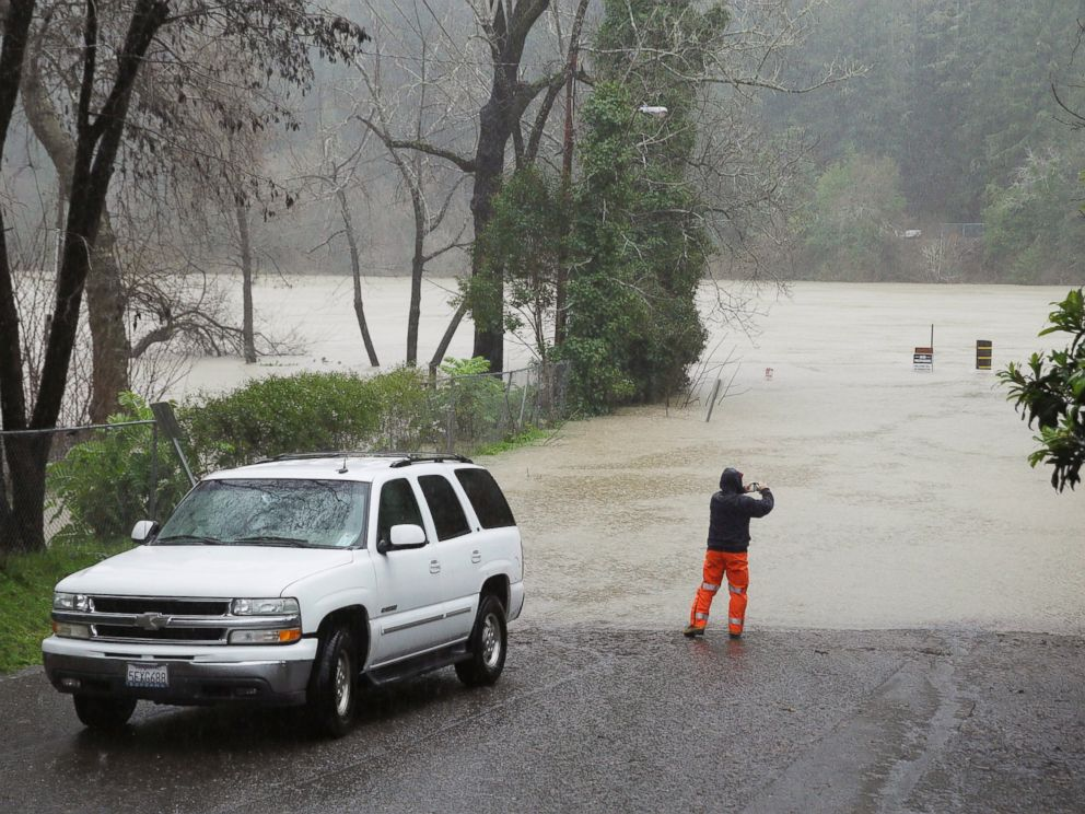 PHOTO: A man stops to take a picture of the Russian River as it floods Johnsons Beach, Jan. 10, 2017, in Guerneville, California.