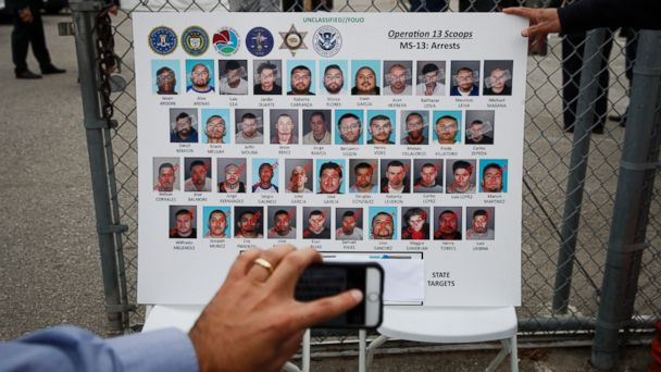 PHOTO: A reporter uses his smartphone to photograph a board showing images of MS-13 gang members during a news conference, May 17, 2017, in Los Angeles.