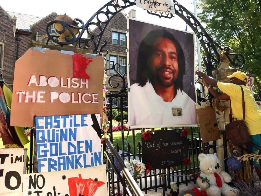 PHOTO: King Demetrius Pendleton hangs a sign on the gate of the Governors Residence in St. Paul, Minn., as protesters demonstrate against the July 6 shooting death of Philando Castile in Falcon Heights, Michigan, July 24, 2016 .