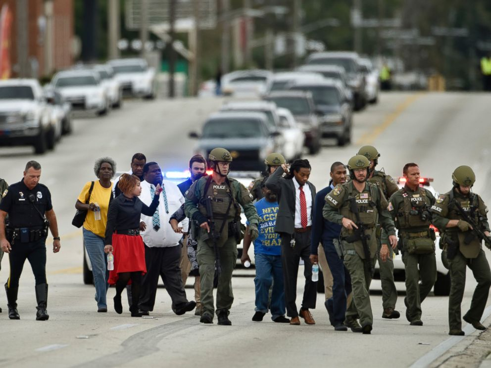 PHOTO: Police officers escort hostages safely across the street after a gunman held them during an attempted robbery at Community First Credit Union, Dec. 1, 2016, in Jacksonville, Florida.