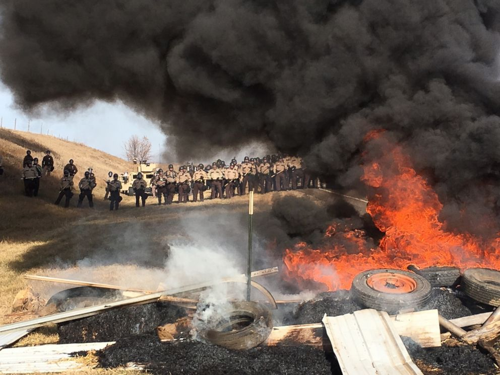 PHOTO: Tires burn as armed soldiers and law enforcement officers stand in formation on Oct. 27, 2016, to force Dakota Access pipeline protesters off private land where they had camped to block construction.