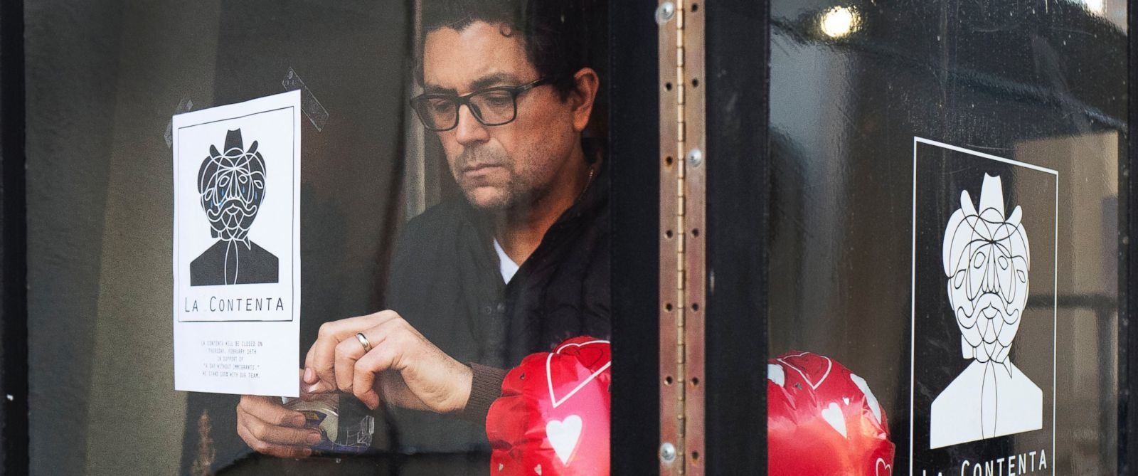 PHOTO: Luis Arce Mota, the chef and co-owner of La Contenta, posts a flyer in the window announcing the closure of his restaurant for the day, Feb. 16, 2017, in New York.