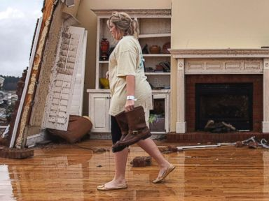 PHOTO: Jenny Bullard carries a pair of boots from her home that was damaged by a tornado, Jan. 22, 2017, in Adel, Georgia.
