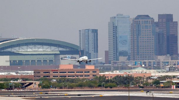 PHOTO: Heat waves ripple across the tarmac at Sky Harbor International Airport as downtown Phoenix stands in the background as an airplane lands, June 20, 2017, in Phoenix.