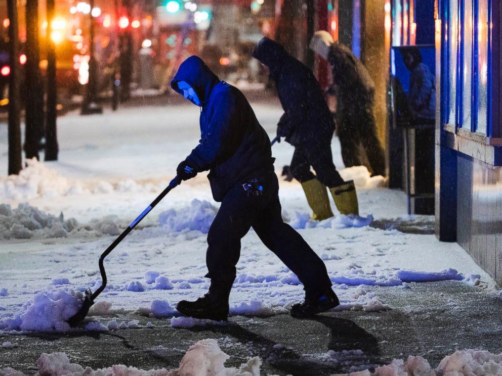 PHOTO: Workmen clear a sidewalk during a winter storm in Philadelphia, March 14, 2017.