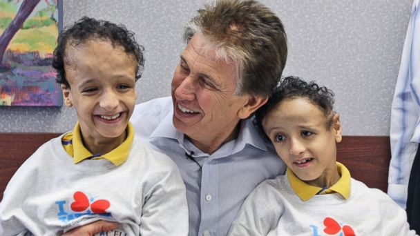PHOTO: Dr. Kenneth Salyer, center, holds twin brothers Mohamed Ibrahim, left, and Ahmed Ibrahim during a welcoming party in Dallas, Texas, Sept. 16, 2009.