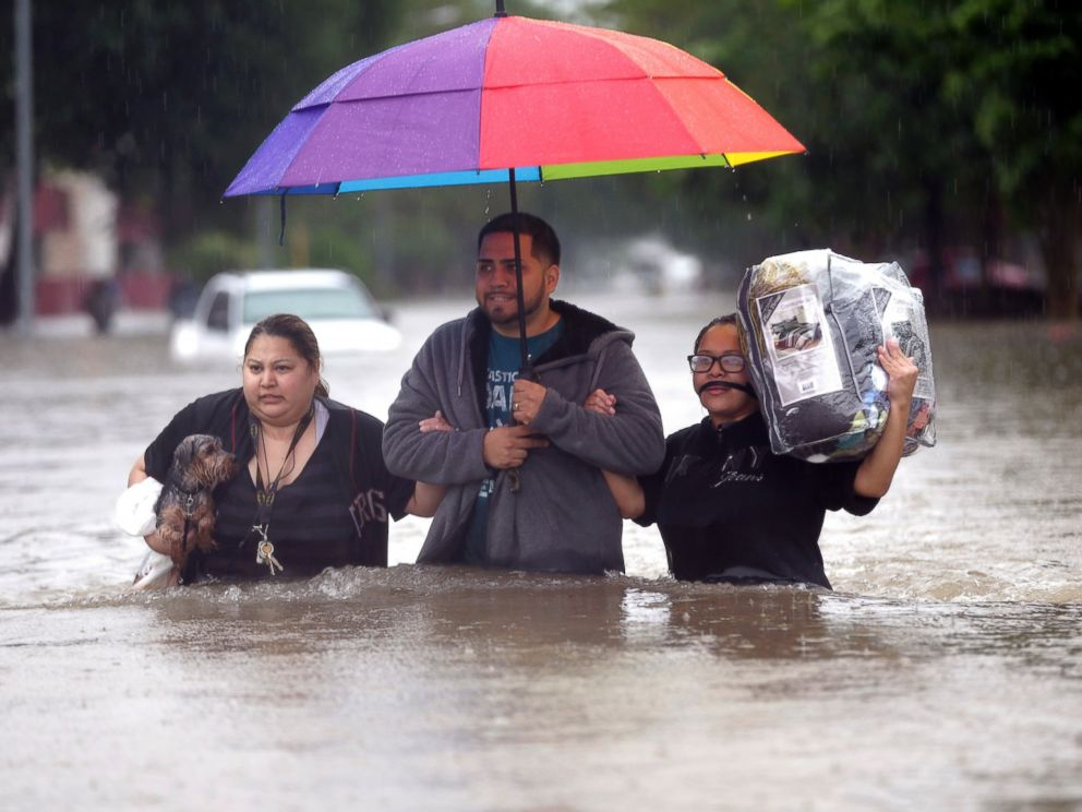 PHOTO: Felix Yanez, center, helps Lucy Olvio, right, and Judy wade through floodwaters as they evacuate from their flooded apartment complex, April 18, 2016, in Houston.