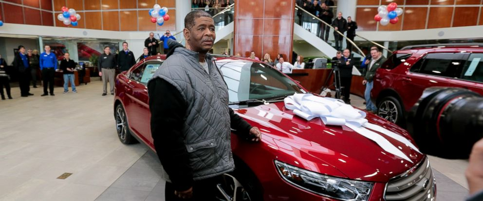 James Robertson, 56, stands next to his free 2015 Ford Taurus from Suburban Ford in Sterling Heights on Feb. 6, 2015, as part of a continuing showing of community support after a story of his dedication and journey on his 21 mile walk to and from work.