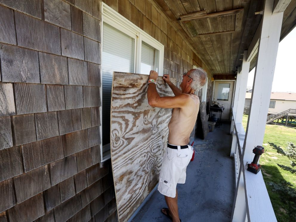 PHOTO: Peter LeWando puts plywood sheets over the windows of his apartment in Avon, N.C., July 3, 2014.
