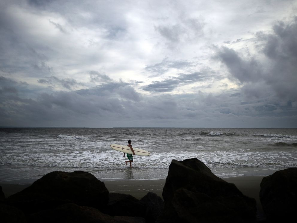 PHOTO: Kevin Taylor of Savannah, Ga., heads out to surf the waves on the north beach of Tybee Island as Hurricane Arthur makes its way up the East Coast, July 3, 2014.