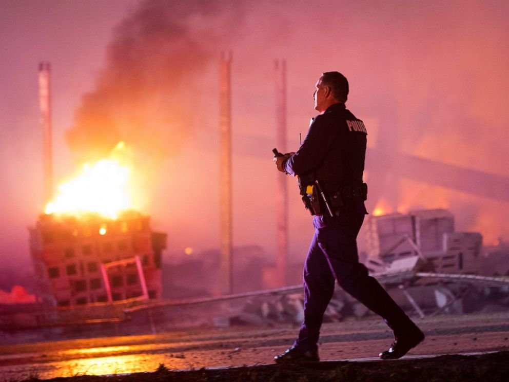PHOTO: A police officer walks by a blaze, April 27, 2015, after violence broke out in Baltimore.
