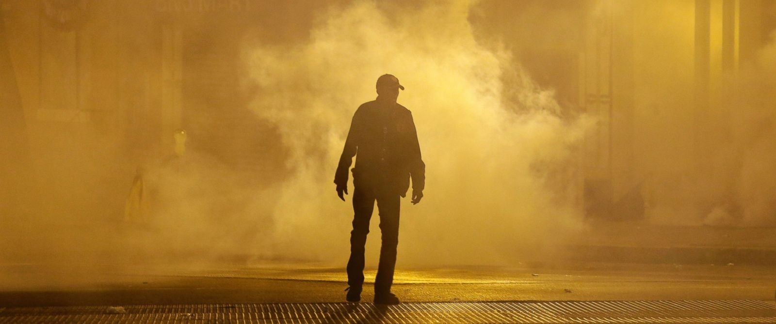A man walks through a cloud of tear gas as police enforce curfew, Tuesday, April 28, 2015, in Baltimore, a day after unrest that occurred following Freddie Grays funeral.