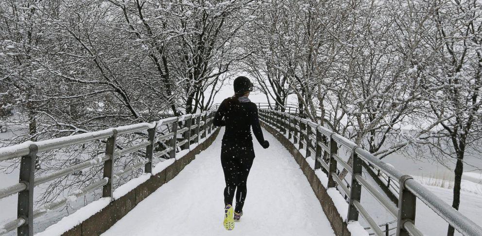A jogger crosses a footbridge to the Esplanade in Boston, Saturday, Jan. 24, 2015.