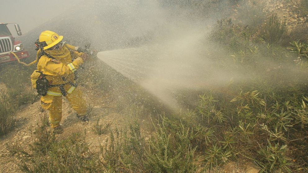 PHOTO: A firefighter sprays down brush as he battles a fire burning in Day Creek near the Etiwanda Preserve in Rancho Cucamonga, Calif., April 30, 2014.