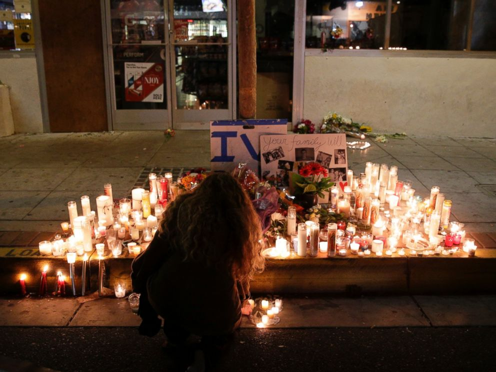 PHOTO: A woman places a candle in front of IV Deli Mart in Isla Vista, Calif., May 24, 2014, following a mass shooting one day earlier.