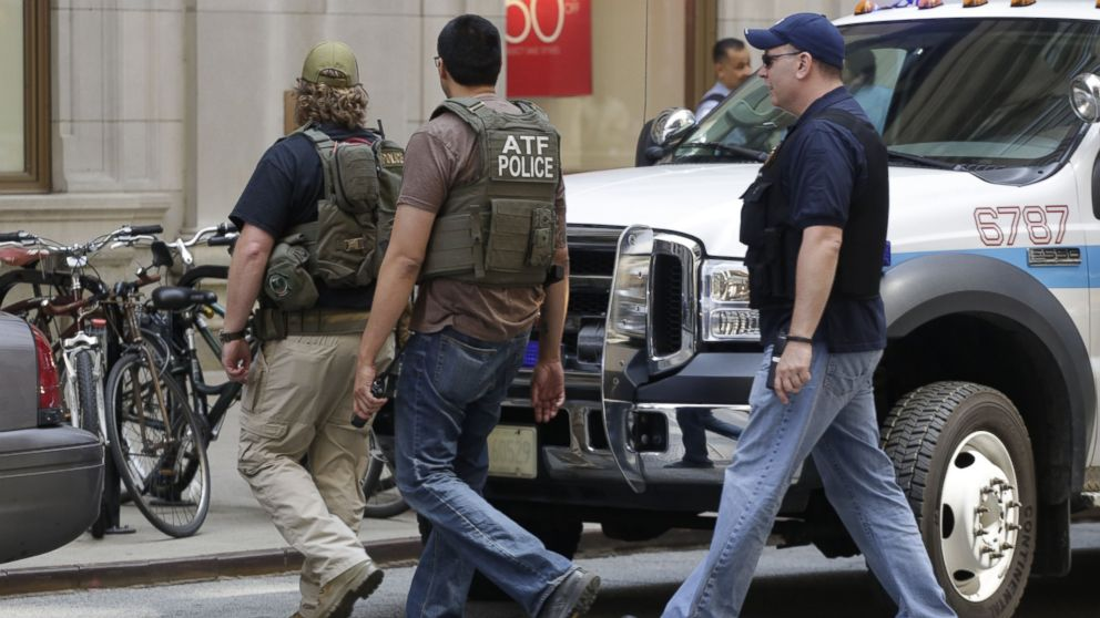 PHOTO: Bureau of Alcohol, Tobacco, Firearms and Explosives agents and Chicago police are seen outside a downtown high-rise office building following a shooting, July 31, 2014, in Chicago.