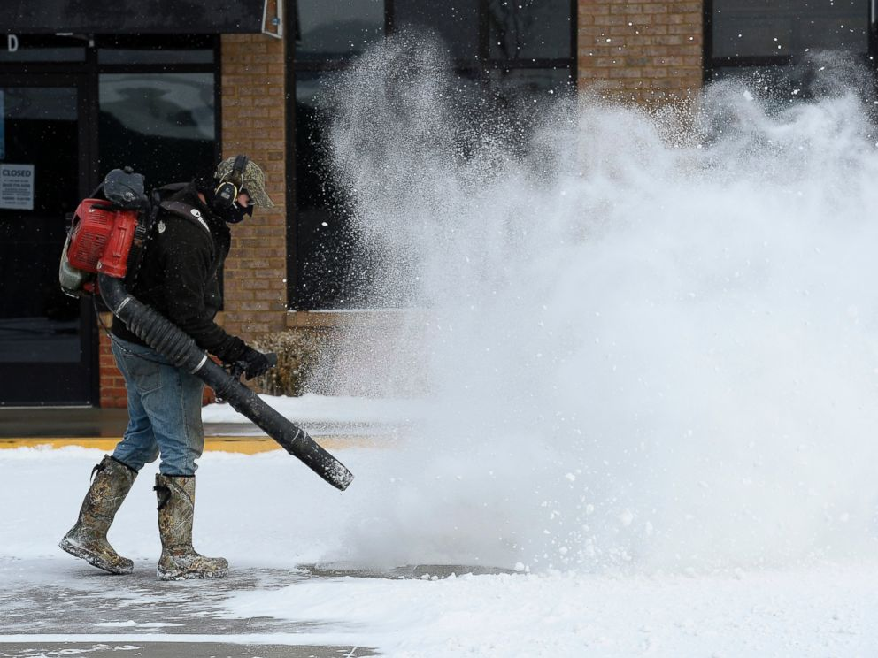 PHOTO: Will Scott uses a blower to remove snow from a parking lot, Feb. 18, 2015, in Nolensville, Tenn.
