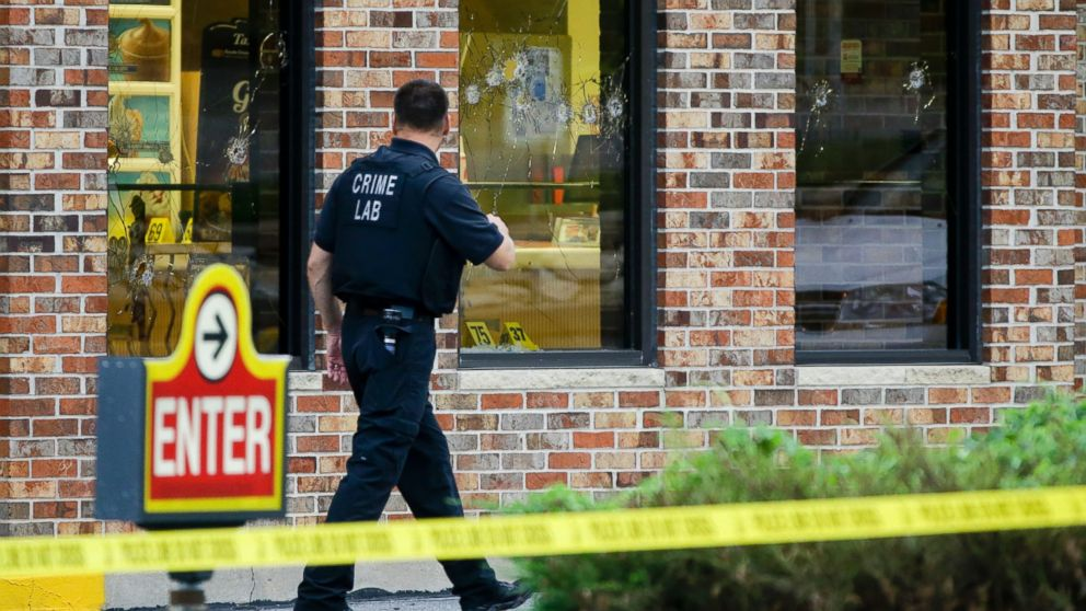 PHOTO: A crime lab technician walks past bullet riddled windows at a Wendys in Omaha, Neb., Aug. 27, 2014.