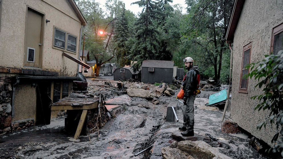 PHOTO: Volunteer rescuer Jesse Rochette searches the Fountain Creek flood waters for anyone trapped or stranded as another flash flood washes off the Waldo Canyon burn scar, Friday, Aug. 9, 2013 in Manitou, Colo.