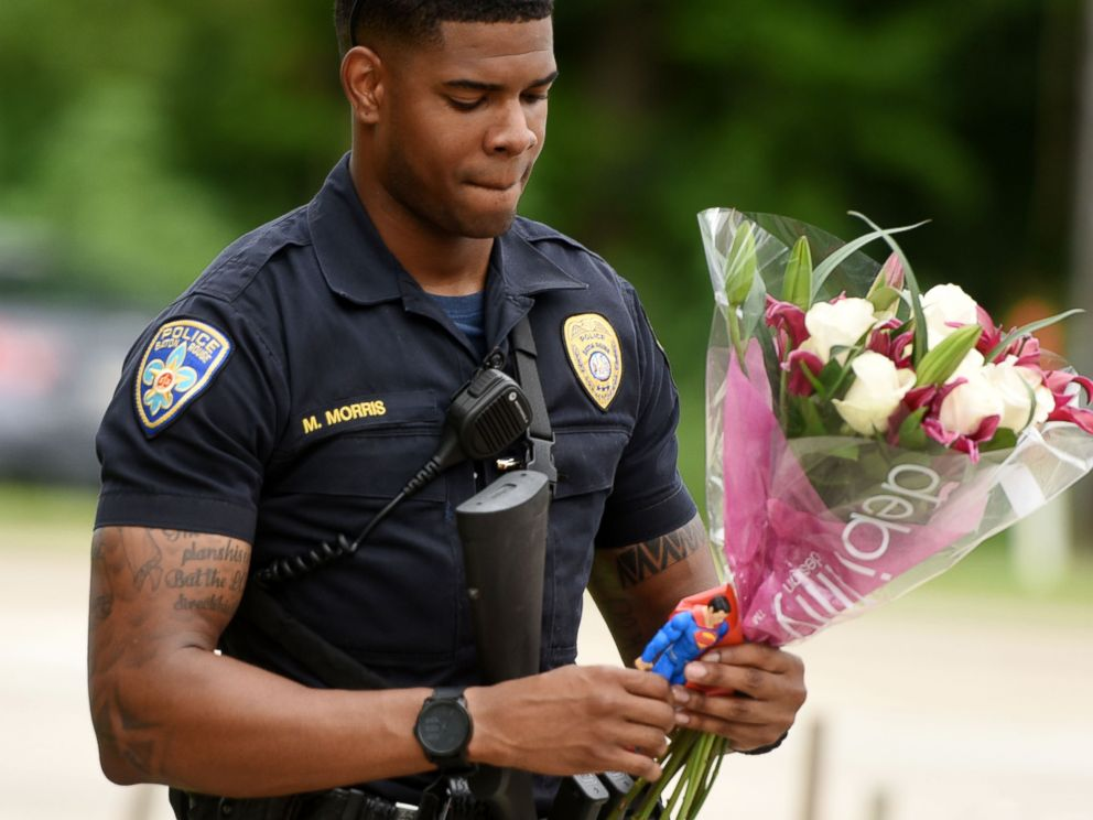 PHOTO: Baton Rouge Police Department Officer Markell Morris holds a bouquet of flowers and a Superman action figure that a citizen left at the Our Lady of the Lake Hospital where the police officers were brought this morning, July 17, 2016.
