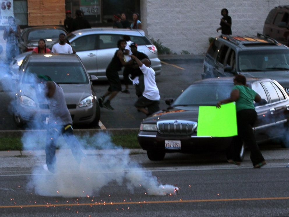 PHOTO: People scatter as police officers fire tear gas, Aug. 11, 2014, in Ferguson, Mo.