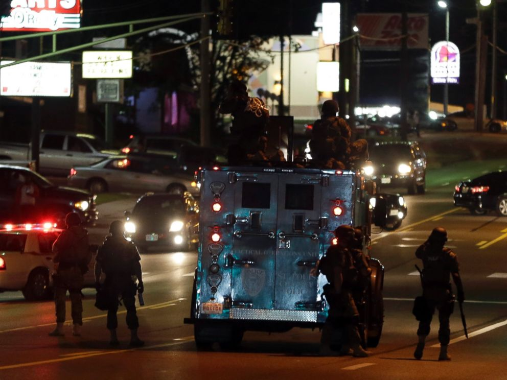 PHOTO: Police attempt to secure a street after a clash with protesters, Aug. 13, 2014, in Ferguson, Mo.