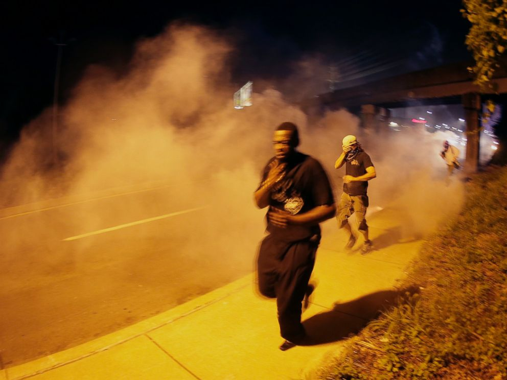 PHOTO: People run after police fired tear gas in Ferguson, Mo., Aug. 17, 2014.