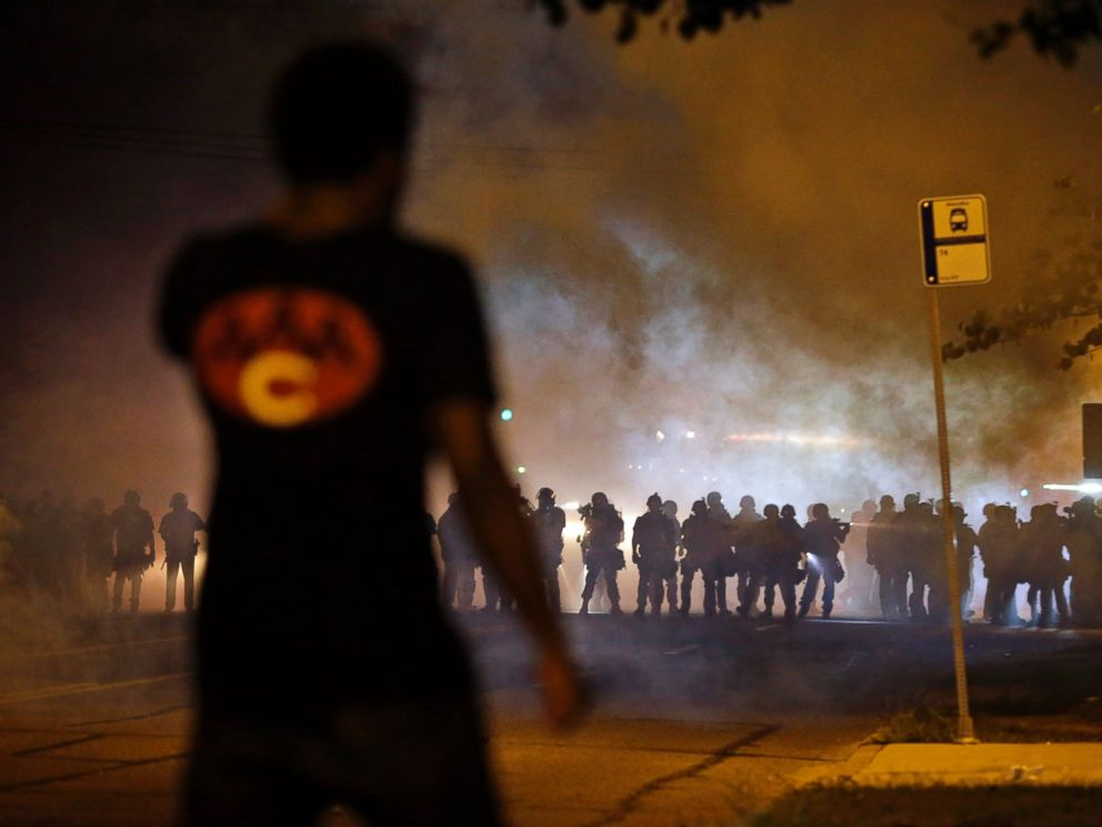 PHOTO: A man watches as police walk through a cloud of smoke during a clash with protesters, Aug. 13, 2014, in Ferguson, Mo.