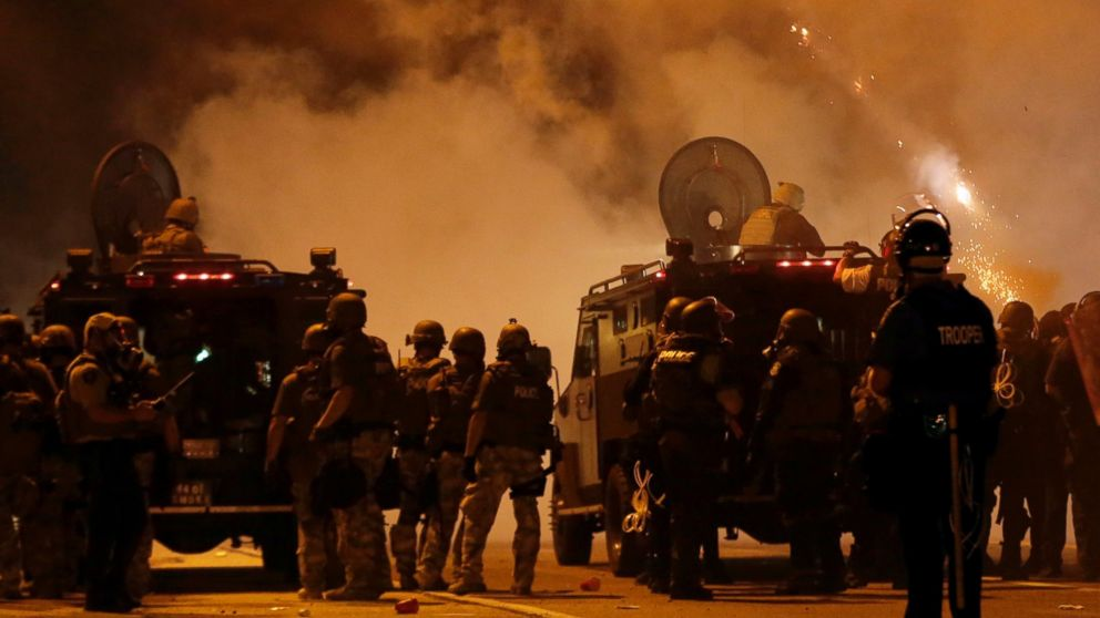 PHOTO: Police wait to advance after tear gas was used to disperse a crowd in Ferguson, Mo., Aug. 17, 2014.