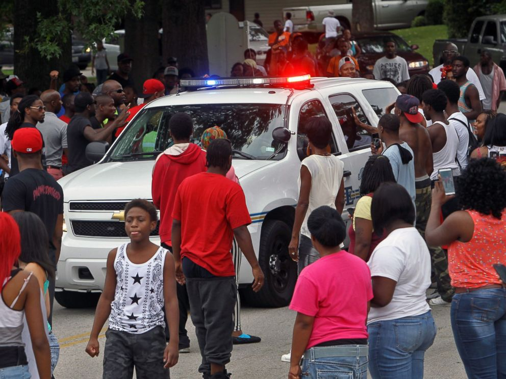 PHOTO: Protesters bang on the side of a police car, Aug. 10, 2014, in Ferguson, Mo.