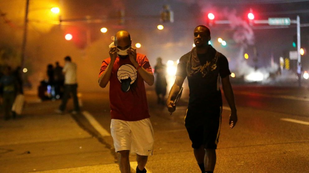 PHOTO: Men walk away from a cloud of tear gas during a protest, Aug. 18, 2014, in Ferguson, Mo.