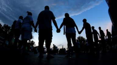 PHOTO: People stand in prayer after marching about a mile to the police station to protest the shooting of Michael Brown, Aug. 20, 2014, in Ferguson, Mo.