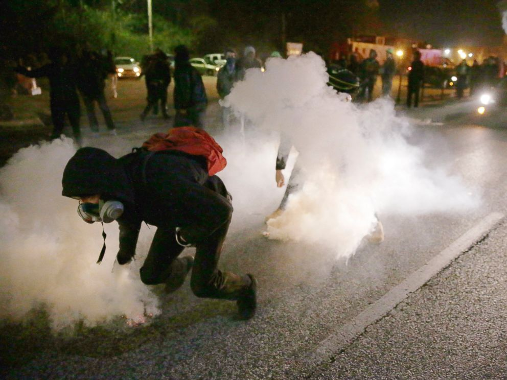 PHOTO: Protesters grab smoke canisters and throw them to police, Nov. 25, 2014, in Ferguson, Mo.