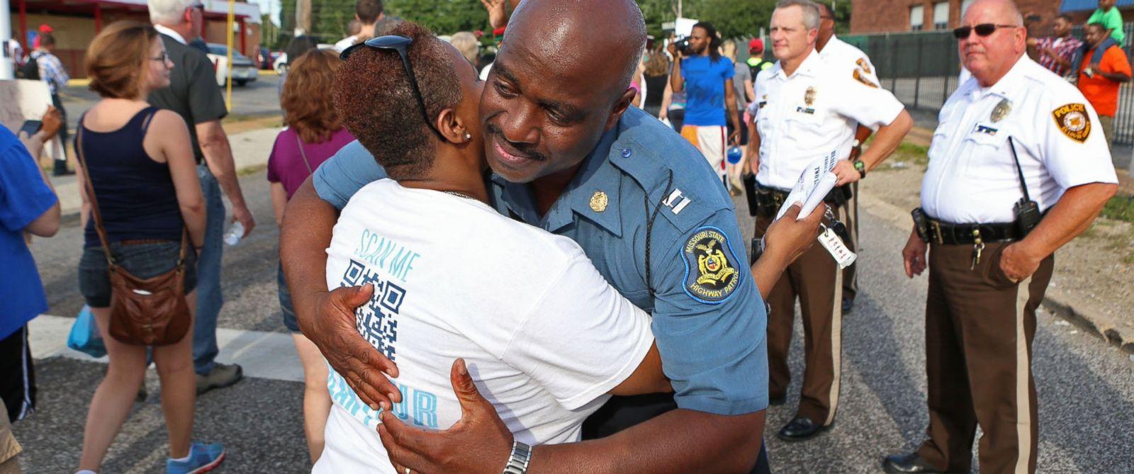 PHOTO: Capt. Ronald Johnson of the Missouri Highway Patrol hugs Angela Whitman, of Berkeley, Mo., on West Florissant Avenue in Ferguson, Mo., Aug. 14, 2014.