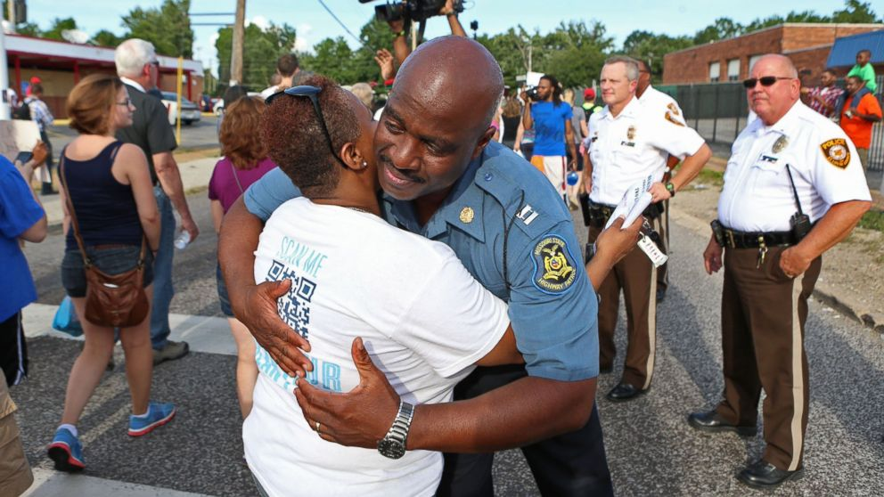 PHOTO: Capt. Ronald Johnson of the Missouri Highway Patrol hugs Angela Whitman, of Berkeley, Mo., on West Florissant Avenue in Ferguson, Mo., Aug. 14, 2014.