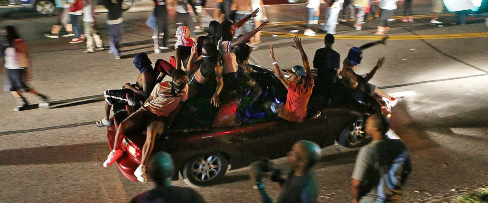 PHOTO: People drive down the street honking their horns, raising their arms, and holding signs on in Ferguson, Mo., Aug. 14, 2014.