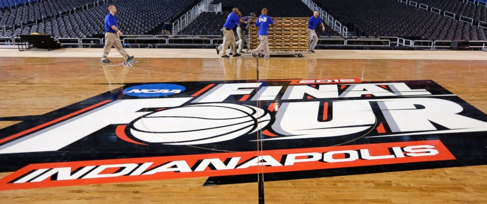 PHOTO: Workers at Lucas Oil Stadium install the court in Indianapolis, March 27, 2015.